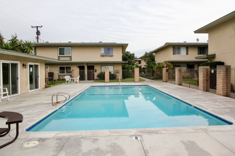 THIS IMAGE VIEWS THE HOME AROUNDBY SWIMMING POOL IN BUENA PARK THAT HAVE THE LAWN, AND SMALL PLANTS, TREES