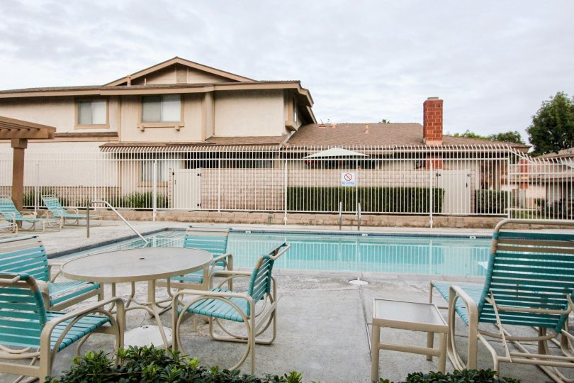 Nice view of swimming pool with chairs near villas in Village park of Buena Park