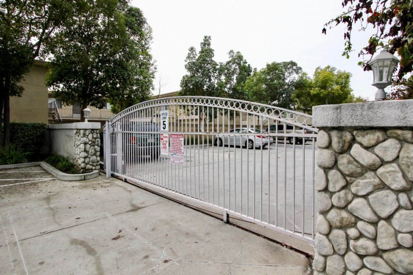 a rainy day in the western bay estates with a building that has parking car and entrance gate closed and stone walls