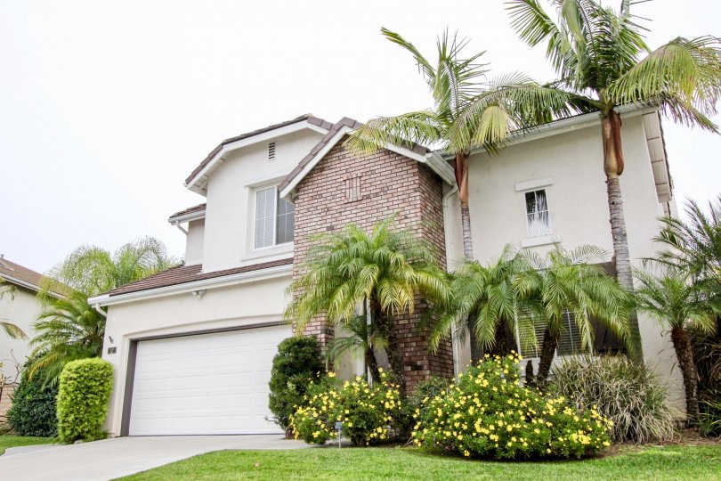 A two-story house with a garage in the Westshore Villas area of Buena Park, CA with palm trees, shrubs, and bushes