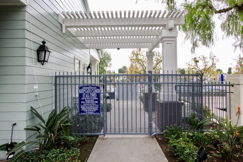 A gate in the Westshore Villas with a blue sign board.