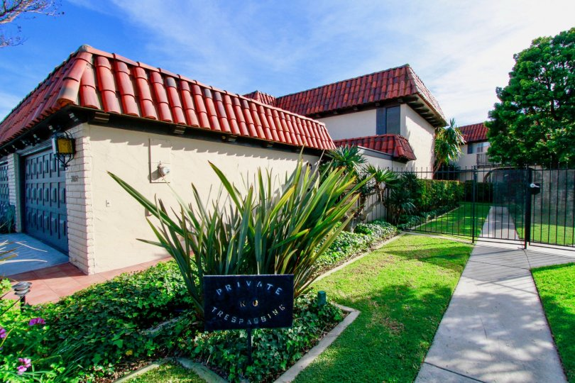 Side view, Spanish style apartments, featuring tile roofs, formal landscaping, Country Club Villas Costa Mesa, California