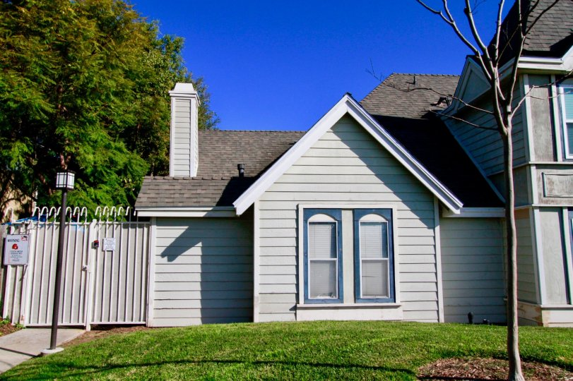 : Knowleton Manor Costa Mesa California building white color paint triangle shape near tree and grasses leafless tree