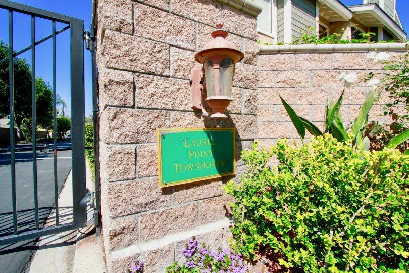 A green Laurel Point entrance sign below a pink light, next to an iron gate.