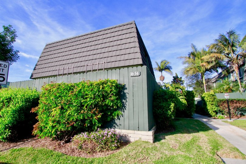A fenced in building surrounded by shrubs in the Mesa Verde Villas community of Costa Mesa CA