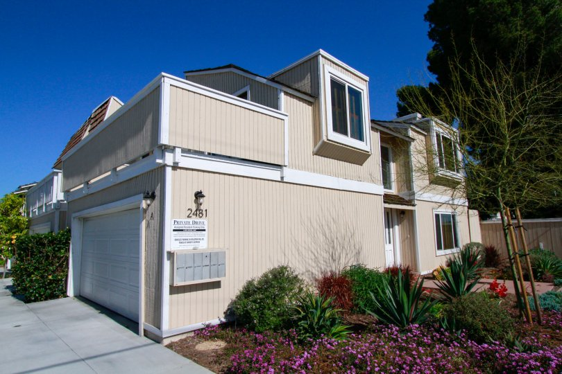 A large tan house with garden on a sunny day in the Newport Chateau community of Costa Mesa CA