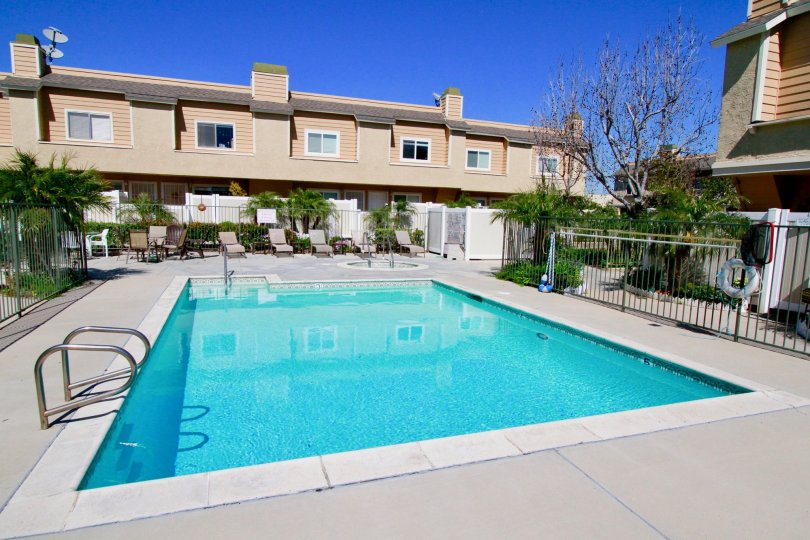 A large blue rectangle pool surrounded by a black iron fence at ocean Breeze Villas in Costa Mesa CA