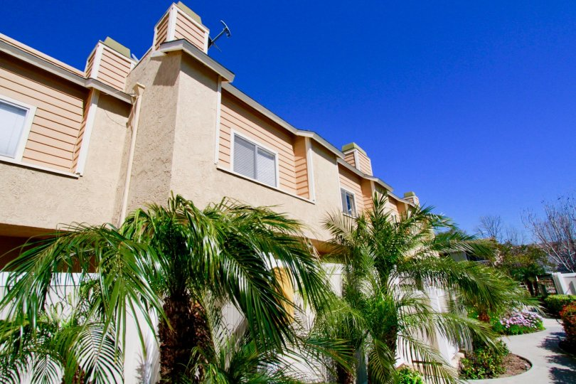 Ocean Breeze Villas apartments with a fence and palm trees.
