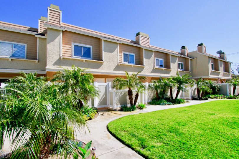 Ocean Breeze Villas apartments with fences and palm trees on a sunny day.