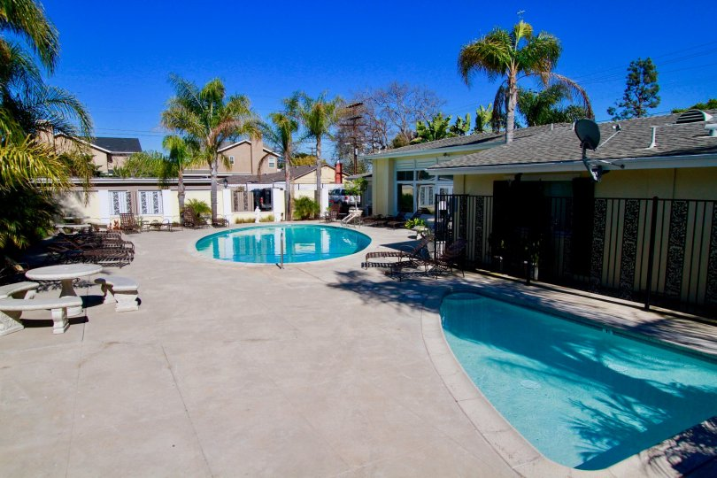 Community pool, kids pool and large outdoor space on a sunny day in the Orleans Townhouse community in Costa Mesa, CA