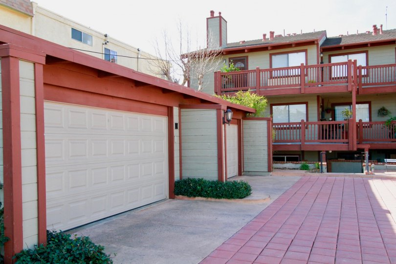 Apartment homes in a bright red and tan design, pictured are garages and 2 porches