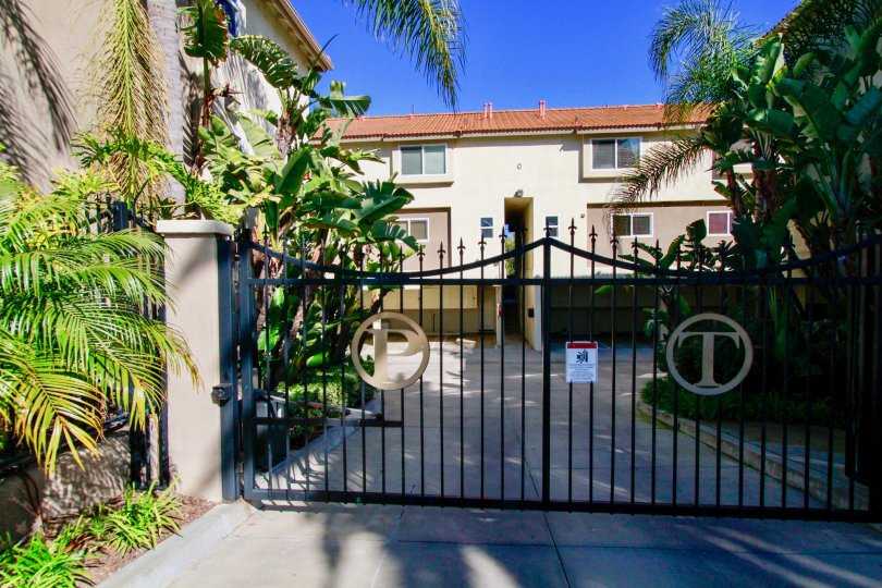 A big house with a big gate in the Palermo Townhomes with palm trees and flowring plants near the road