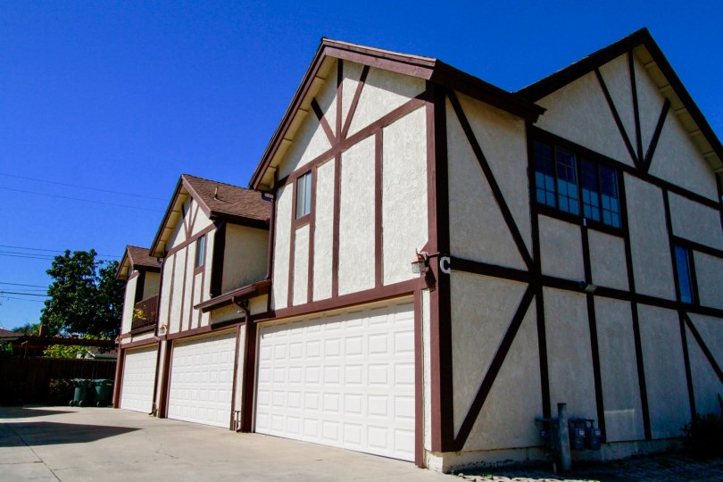 Row of white stucco two-story units with brown accenting and dual garages at Picadilly Terrace in Costa Mesa, CA