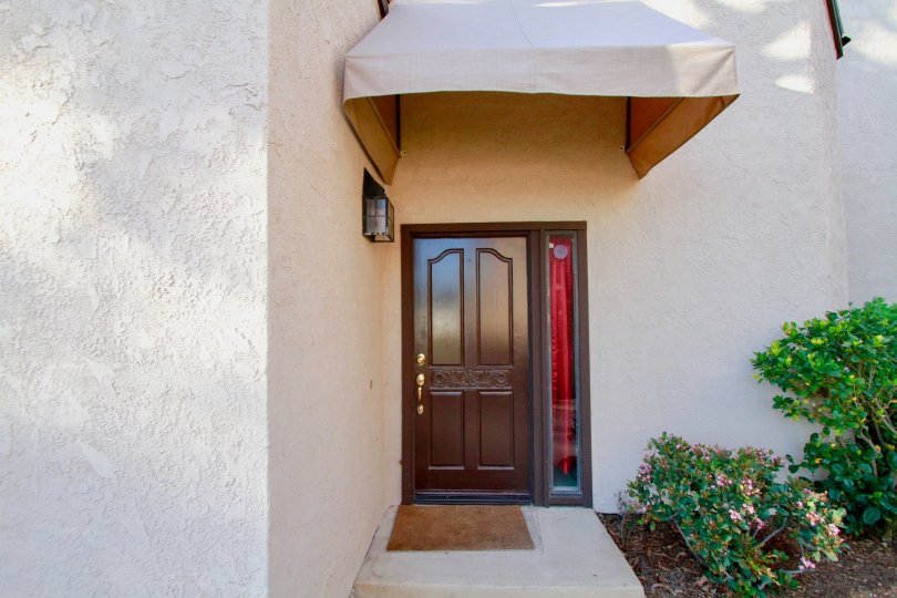 Polished, wooden door, with canopy, hedges, Sommerset, Costa Mesa, California