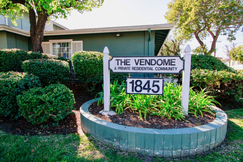 The Vendome sign with plants and trees on a sunny day.