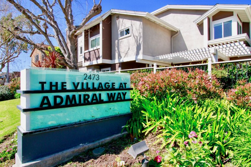 THE BOARD SIGN REPRESENTS THE VILLAGE AT ADMIRAL WAY AND IT LOOK LIKE BLUE BACKGROUND AND THE BUILDING ALSO LOCATED AT THE BACK SIDE OF THE BOARD SOME PLANTS NEAR TO THE SIGN