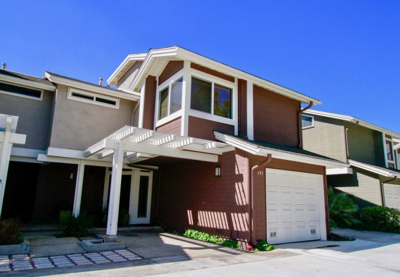 Two story brown condo with attached garage with white door at The Village At Admiral Way in Costa Mesa CA