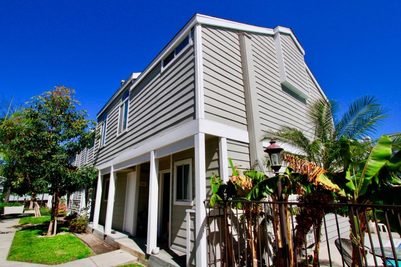 A two story condo home with gray wooden palens locatedi n Costa Mesa in Victoria Garden Villas