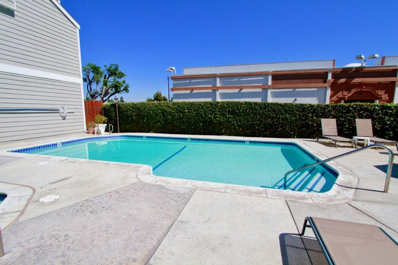 A oddly shaped crystal blue pool with steps and railing at Victoria Garden Villas in Costa Mesa CA