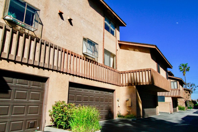 Three large brown garage doors attached to the base of town homes in Villa Maple in Costa Mesa CA