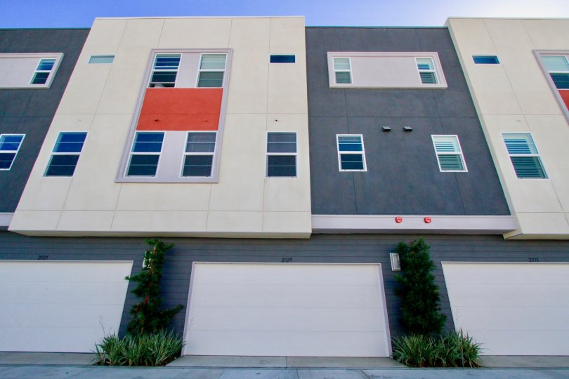 A large three story structure with a red cloth covered window at West Place in Costa Mesa CA