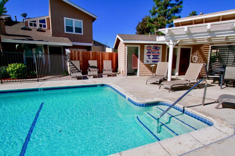 Woodstream Condos Costa Mesa California bulding near to one big size swming pool and steps water blue color very nice home near two wood bad attached daily take the sun both very use