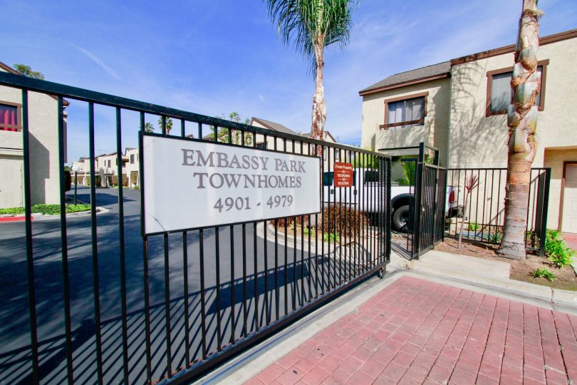 Embassy Park Townhomes Cypress California have long security grid and sign board at front