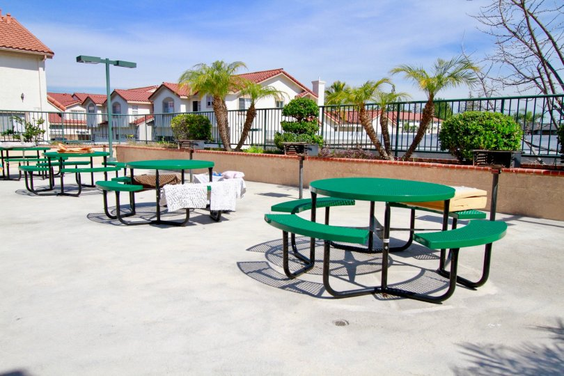 four green round picnic tables with grills placed on concrete slab near houses, towels drying on table benches