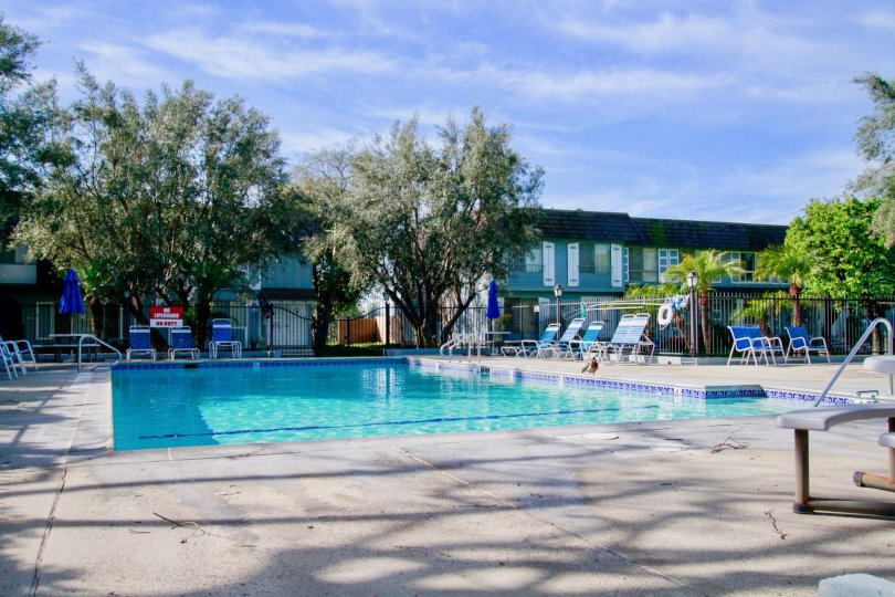 A SWIMMING POOL WITH SOME REST CHAIRS AND PLANTS ALSO AVAILABLE AND A GOOD RESTAURANT ALSO SURROUNDING THERE