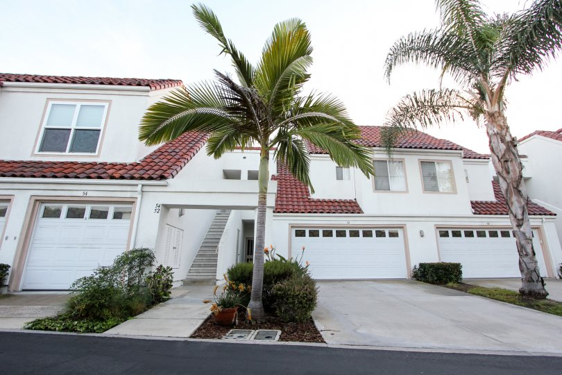 Front view with trees, garage door and staircase of Encantamar community, Dana Point, CA