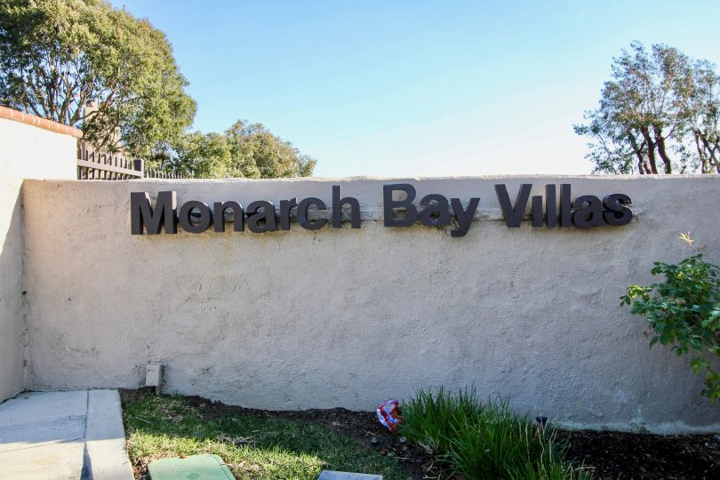 a sunny day in the monarch bay villas with a compound wall that has the name board of the community