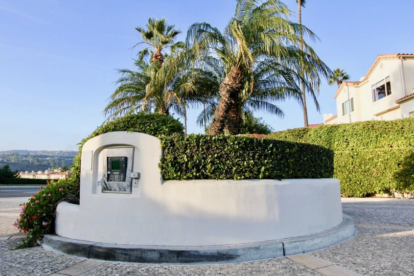 A round cement island with an intercom on it's side at Tennis Villas in Dana Point CA
