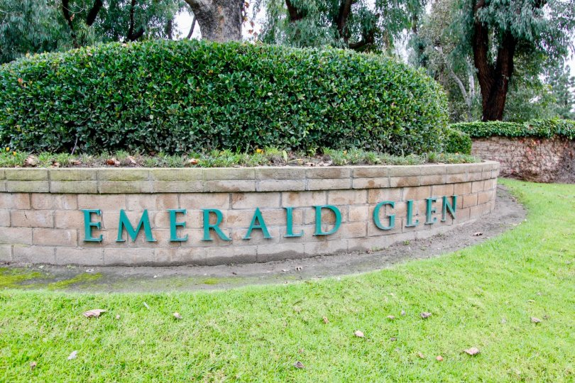 An entrance area with bushes on top and writtien with green letter showing the community Emerald Glen.