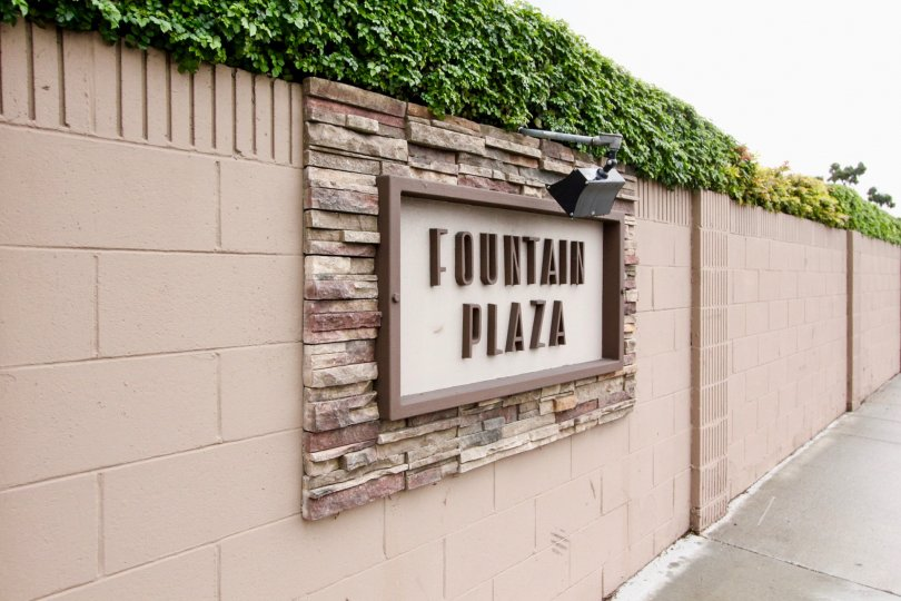 A long tan wall with the sign pictured in tan and brown in the Fountain Plaza community.