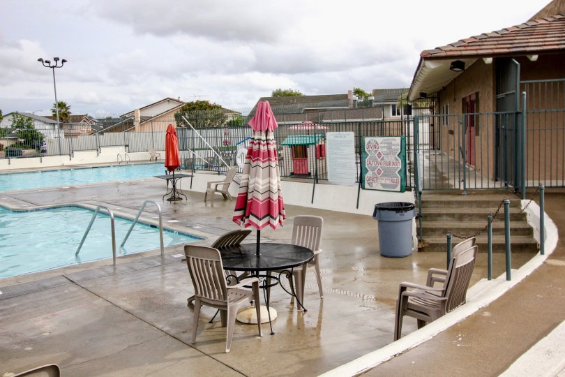 A beautiful swimming pool in the Green Valley Townhomes with buldings, resting chairs and table.