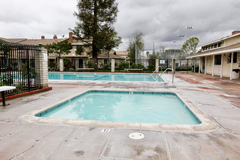 A long rectangle pool sits next to a square hot tub at Harbor Valley in Fountain Valley CA