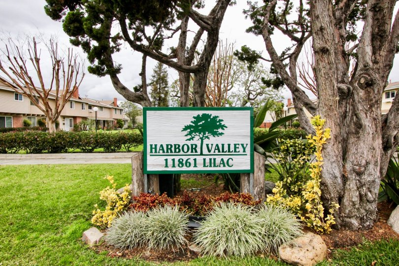 Entrance sign to community in white and green in color saying Harbor Valley.
