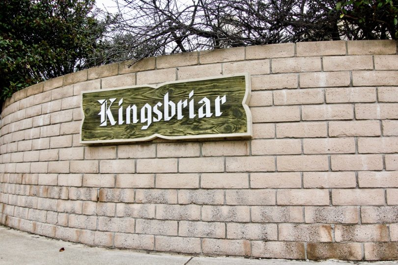 Entrance sign backing made of bricks and the sign is wood and cream lettering showing the community name Kingsbriar.