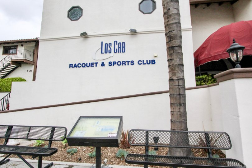 Los Cab Racquet & Sports Club sign in the color blue and background cream located in Los Caballeros community.