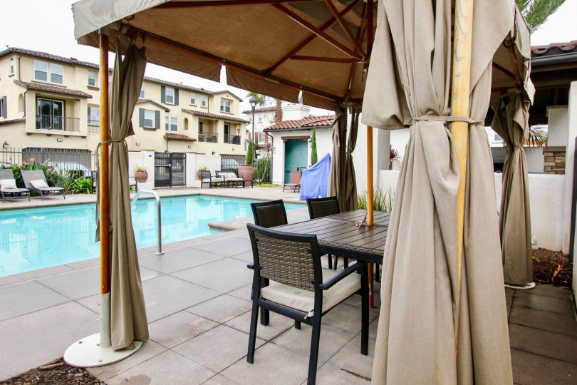 A swimming pool in the Solana Walk with beautiful buldings, resting room with chairs and tables, shrubs.