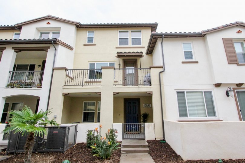 Multi level residential homes with balconies and porches with plants in front located in Solana Walk community.