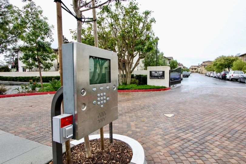 at the road in Solana walk has telephone booth with trees, lawn and plants