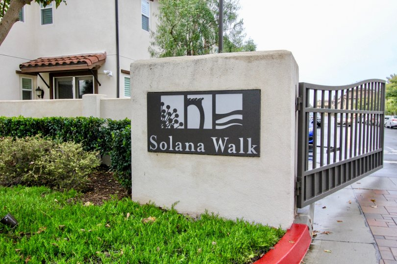 Front to the gate in Solana walk has grasses with trees and cutting bushes at fountain valley city