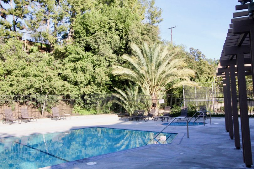 In the Amberwood community is a pool with a shaded sitting area and a gate around the pool with trees.