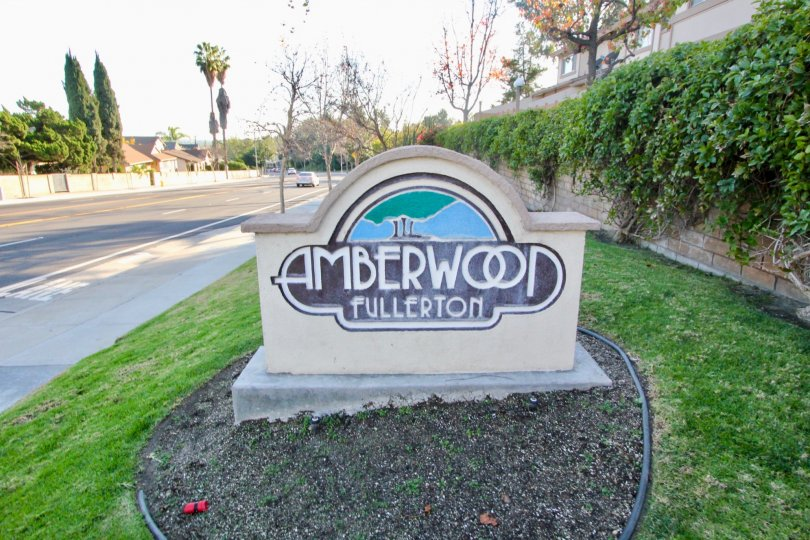 Amberwood entrance sign next to a street on a sunny day.