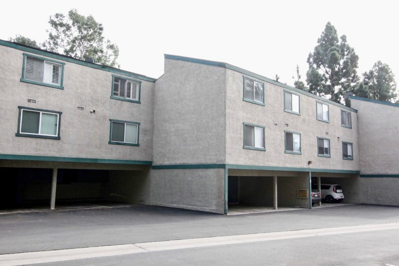 Gray apartment building in Brea Country with parking spaces and green trim.