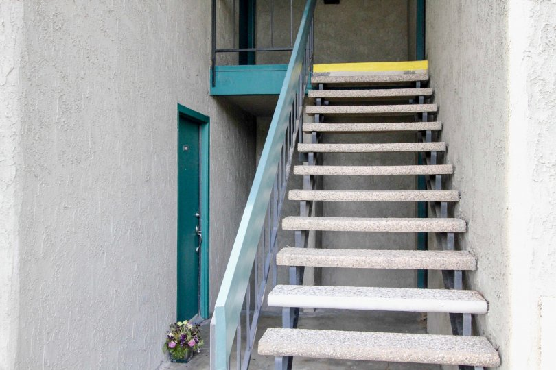 Gray stucco open stairwell leads to turquoise doors in Brea Country community of Fullerton, CA.