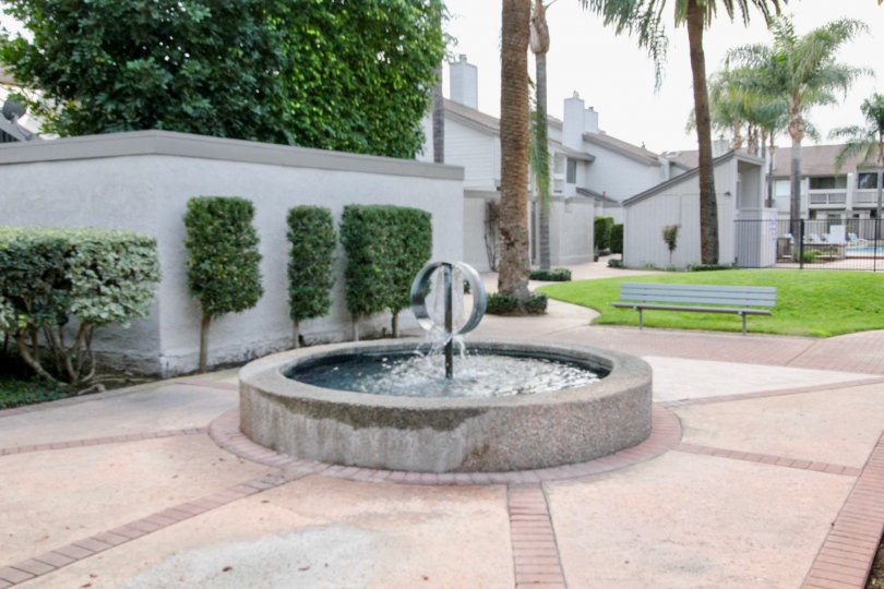 In pathway, Fountain with water and bench are fixed at center in Chapman Villas