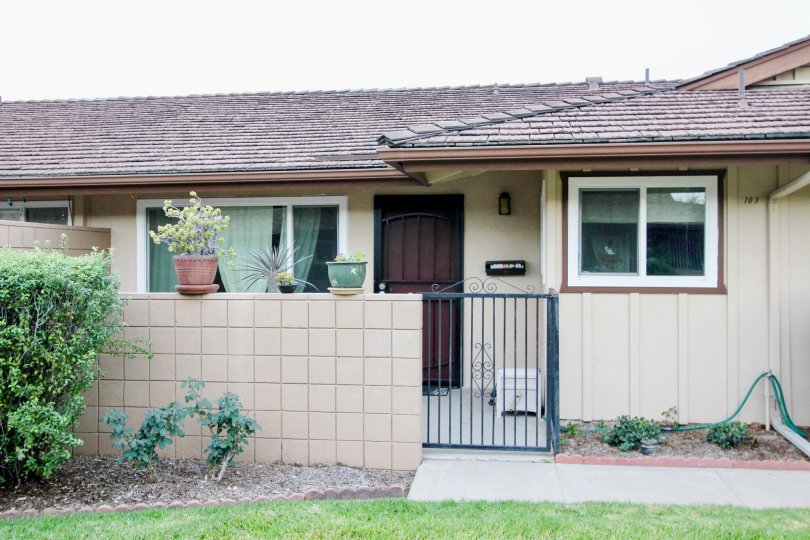 A single story home with a black iron gate near it's front door at coco Palms in Fullerton CA