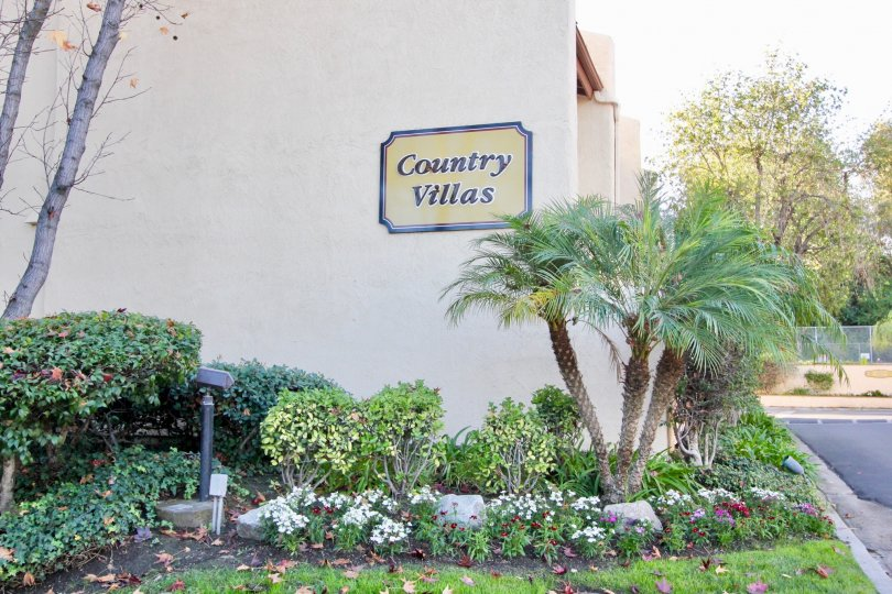 A sign for the Country Villas community with assorted plants in a garden.